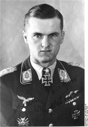The head and shoulders of a young man, shown in semi-profile. He wears a military uniform with an Iron Cross displayed at the front of his shirt collar. His hair is short and combed to his right, his nose is short, and his facial expression is determined; looking into the camera.