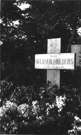Black-and-white photograph of a wooden cross on a grave, bearing the inscription