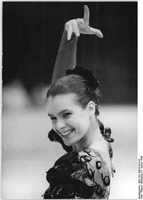 A young smiling woman wearing a traditional Spanish flamenco dress and head gear, and executing the typical flamenco posture.