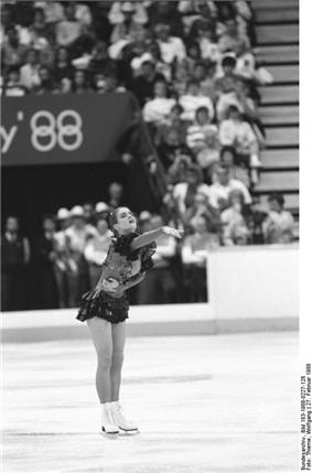 A female figure skater points with her right arm as she performs