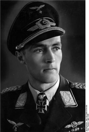The head and shoulders of a young man, shown in semi-profile. He wears a peaked cap and a military uniform with an Eagle above his right and a military decorations above left breast pocket, and an Iron Cross displayed at the front of his shirt collar. His facial expression is determined; his eyes are looking into the distance to the left of the camera.