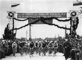 A black-and-white photograph showing a group of cyclists, with a banner above them