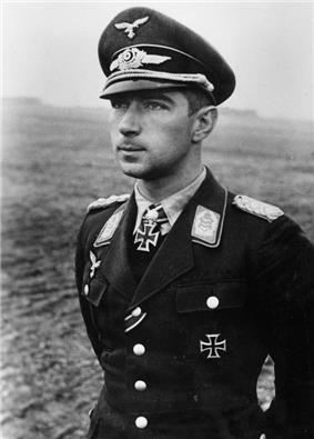 Black-and-white photograph showing the face and upper body of a young man in uniform, his hands behind his back, standing in a featureless landscape. His cap and the front right of his jacket bear eagle-and-swastika emblems; the front left of his jacket and the front of his shirt collar bear Iron Cross decorations, black with light outline. He is shown in semi-profile, gazing at a point in the distance to the left of the camera, his facial expression confident.