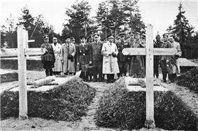17 men, most in military uniform, stand in a cemetery, inspecting two graves.