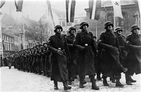 a black and white photograph of soldiers in German uniform and greatcoats marching in a column