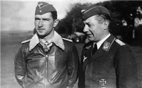 Black-and-white photograph showing half-length view of two uniformed men outdoors, standing next to each other. The young man on the left is wearing a field cap and a pilot's leather jacket with fur collar, with an Iron Cross displayed at the front of his shirt collar. The middle-aged man on the right is shown in three-quarter profile; he is smiling and wears a jacket with military decorations.