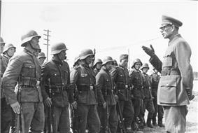 a black and white photograph of a bespectacled Andrey Vlasov in German uniform addressing some soldiers