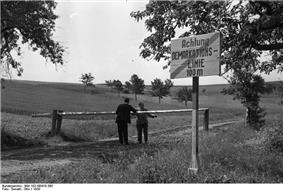 Two people stand either side of a lowered border pole on a dirt road with a sign in the foreground