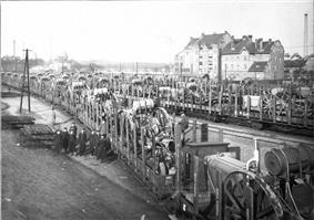 Several trains loaded with machinery take up the center of the photo. A group of nine men stand to the left.