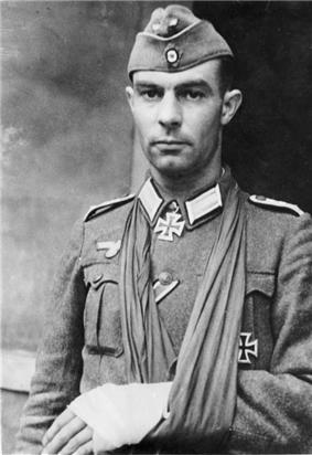 Black and white portrait of a man with his left arm in a sling and wearing a military uniform