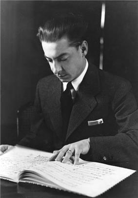 young man with slicked back dark hair, looking down at a musical score