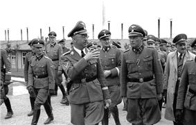 A group of Nazi officers, including Heinrich Himmler, Franz Ziereis, Karl Wolff and August Eigruber shown walking and talking through the camp, with one of the huts in the background.