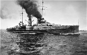 A large gray warship sails through calm seas; a dark cloud of smoke pours out of its two smoke stacks.
