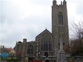 A flint church seen from the west, showing from the right, the tower and the west ends of the nave and the north aisle