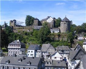 Slate-roofs of Monschau town centre and castle. The castle's courtyard in preparation for Monschau Open Air Klassik music festival