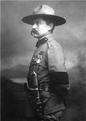 Photo of Burnham taken in 1901 in London after his investiture with the cross of the Distinguished Service Order by King Edward VII.  He is dressed in British Army uniform and standing at attention, facing right.  On his left arm is a black armband worn in mourning for the recent death of Queen Victoria. He is wearing his stetson hat and a sword on his left side. He sports a large handlebar mustache.