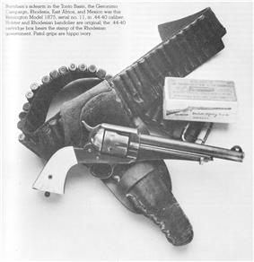 Caption reads: Burnham's sidearm in the Tonto Basin, the Geronimo Campaign, Rhodesia, East Africa, and Mexico was this Remington Model 1875, serial no. 11, in .44-40 caliber. Holster and Rhodesian bandoleer are original; the .44-40 cartridge box bears the stamp of the Rhodesian government. Pistol grips are hippo ivory.