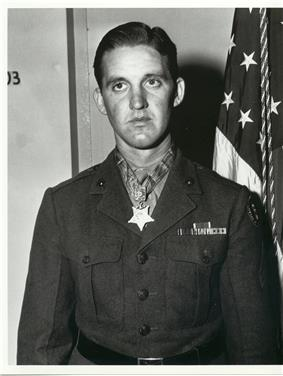 Head and torso of a young white man with neatly combed hair wearing a dark military jacket with a wide belt and a few ribbon bars on the left breast. A star-shaped medal hangs from a ribbon around his neck.