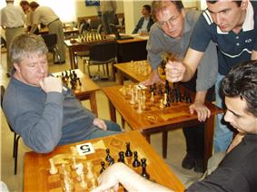 A picture of four men looking over a chessboard and gesticulating. In the background are other chess boards on tables, set up differently.