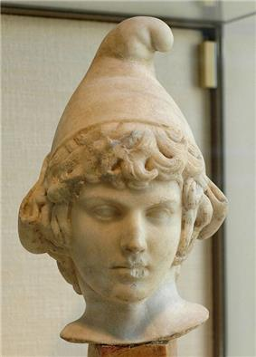 A marble bust of a curly-haired boy wearing an edgeless conical cap with the rounded peak bending forward