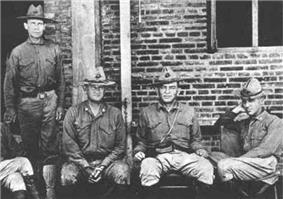 Four men in military uniforms wearing hats. Three are seated on a bench and one is standing behind the others.