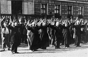 Prisoner priests and laypeople, with their hands up