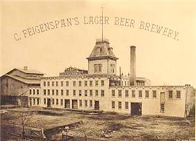 A black and white image of a factory with a steeple, a smokestack, and the caption
