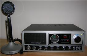 Black-and-gray 1980s-era base station, with tall round desk microphone
