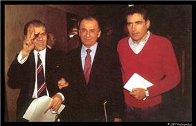 Three men are walking side-by-side holding papers. The first two are wearing a suit and the third is wearing a red sweater. The first man is smiling and flashing a V sign.