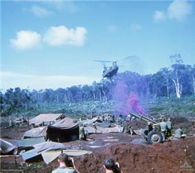 Colour image of a large two-rotored helicopter flying past a line of trees and preparing to land in an open area cleared of vegetation. In the foreground are a large number of tents, hootchies and ground sheets, while a number of soldiers are standing around an artillery piece. Purple smoke is rising from the position.