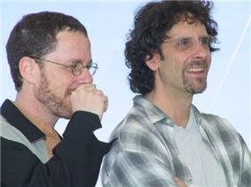 Photo of two Caucasian facing toward their left. The one on the left has short hair, is wearing a black and grey unbuttoned collared shirt, and has his right hand covering his mouth. The one on the right has long curly hair and is wearing a white T-shirt underneath a completely unbuttoned grey and black plaid collared shirt.