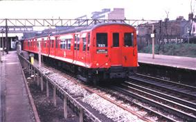 A three-quarter photograph of a red train with sliding doors and flared sides.