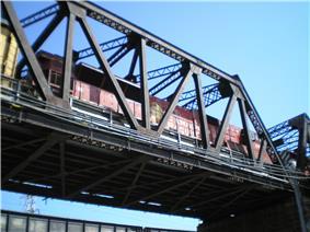 A steel truss bridge with a locomotive on it.