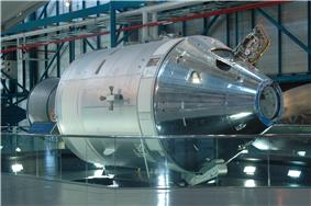 A metallic gray space capsule connected to a cylindrical module lies on its side as a museum exhibit