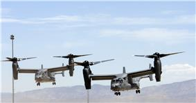 Two USAF CV-22s in a staggered pattern with their rotors vertical preparing to land at Holloman Air Force Base, New Mexico.