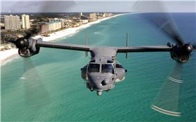 A front view of a U.S. Air Force CV-22 with its rotors facing forward flying over the Emerald Coast of Florida.