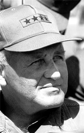 Headshot of an older caucasian man looking off camera while wearing a cap with four stars on it.