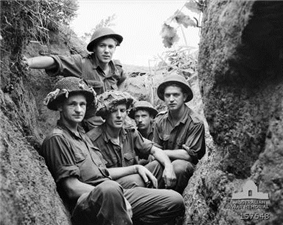 Five young Caucasian men in uniform wearing helmets sit below ground in a trench, facing the camera. The trench is central to the photograph and runs away from it, with the edges of the earthworks on each side. In the background, the skyline can be seen to the rear of the men, framed by the edges of the trench which are covered in roots, grass and other vegetation.