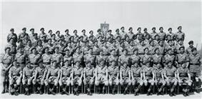 A formative black-and-white photograph of military personnel. The men wear khaki shirts and shorts with long, dark-coloured socks. They all wear dark berets.