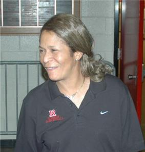 A woman looking to her right. She is wearing a grey polo inscribed with the Nike and Rutgers logos.