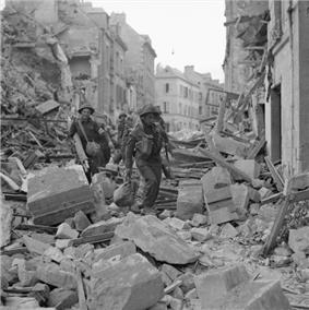 A line of soldiers carefully clambering over the heaped rubble of destroyed buildings in a badly-damaged street
