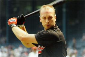A man with short hair prepares to swing a baseball bat. He is wearing a black shirt with