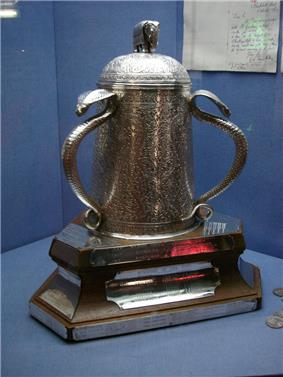 In a blue display cabinet is a bell shaped silver cup which is heavily engraved with patterns; it is adorned on its lid with a small silver elephant and both its large handles are silver cobras.