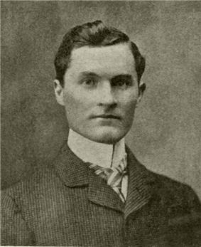 A dark-haired man in his early thirties wearing a high-collared shirt and light-colored jacket, facing left