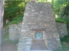 A fieldstone iron furnace with a metal plaque reading