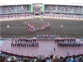 Approximately 50 people in red, black and white uniforms stand on a stage as a team of riders on horseback carry Canadian Flags in the background.