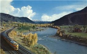 View of a light blue river flowing through a forested valley, with a train running alongside at left and snowcapped peaks in the background