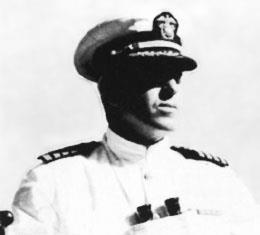 Head and shoulders of a man in a white jacket with black shoulderboards with binoculars hanging from around his neck. His eyes are shaded by a white peaked cap with a black visor.
