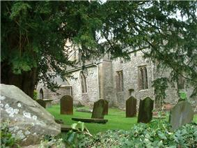 Side of stone building with arched windows, partially obscured by trees. Gravestones in the foreground
