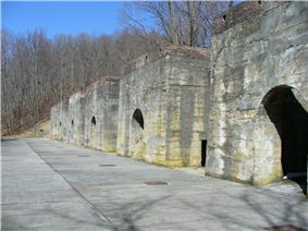 A row of six large stone structures with arched openings, leafless trees are in the background.